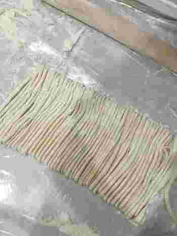 踏み込みが終わった生地を寝かせたら、打ち粉をしながら麺棒でのばし、厚さ3mm程度に。その後、たたんで麺切りします。