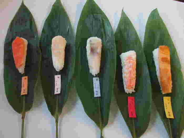 いぐさの紐をほどくと、中から一口サイズのお寿司が出現。鯛や海老、鱒、鯵、玉子と季節のお魚のラインナップで、笹の香りがふわりと広がります。