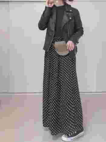 ベージュの小ぶりなウエストバッグを、ドットスカートのウエストマークに活用。全体を黒でまとめたコーディネートの中で、ベージュのバッグが程良い差し色になっています。