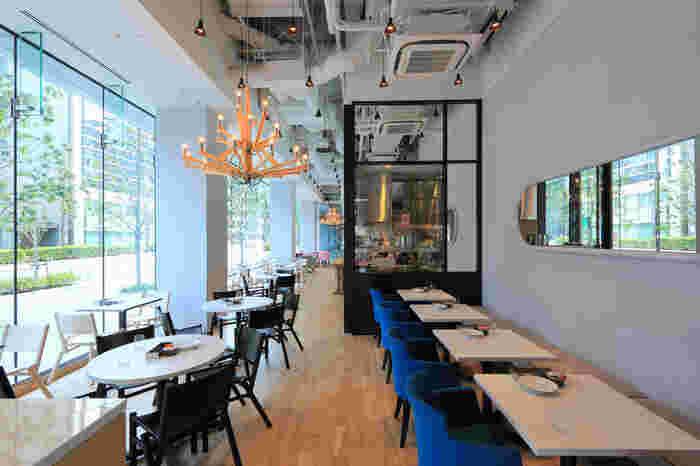 店内は天井が高く、大きな窓から光が降り注ぐ気持ちの良い空間です。椅子やテーブルは様々な形や色があり、インテリアにもこだわりを感じます。