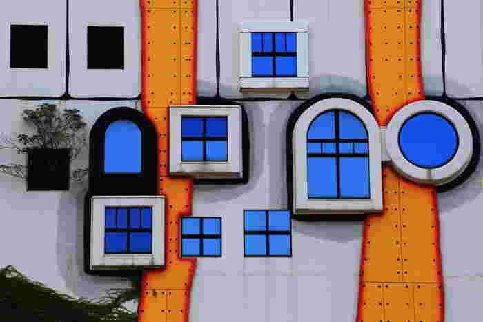 フリーデンスライヒ・フンデルトヴァッサー(Fridensreich Hundertwasser)は、1928年オーストリア・ウィーン生まれの芸術家。2000年没。 もともとは絵画を描いていたフンデルトヴァッサー氏。まるでおとぎ話の世界のような個性的なデザインは、建築を先に学んだ人とは一味違う、絵画の延長という印象があります。また、生涯において「自然との調和」を目指す彼の作品の特徴のひとつとして、「自然界に直線はない」という考えのもと、既定のドアや窓の枠以外には直線のデザインが極力使われていないそうです。