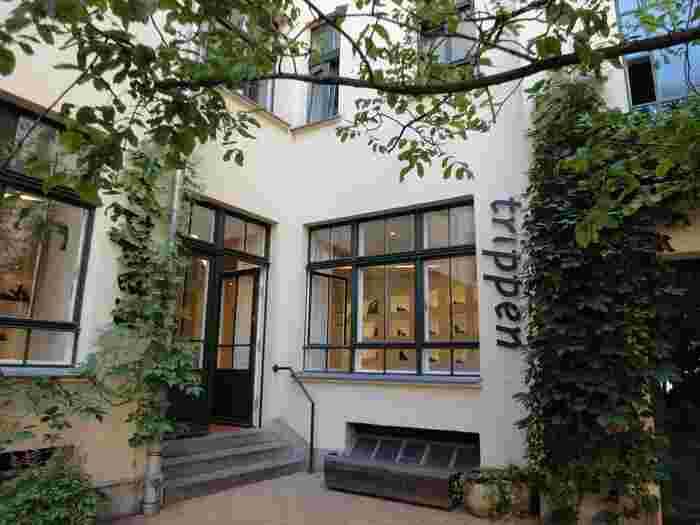 「trippen(トリッペン)」は、独特のカルチャーで注目されるドイツ・ベルリンの、さらに濃いカルチャーを体感できる地区、ハッケシェヘーフェを拠点とするシューズメーカーです。  1992年、ベルリンの小さなアートギャラリーで、医療用矯正靴(コンフォートシューズ)の製作に携わっていたミヒャエル・エーラー氏と、デザイナーのアンジェラ・シュピーツ氏の二人が木製靴を展示した事が、ブランドとしてのスタートとなりました。