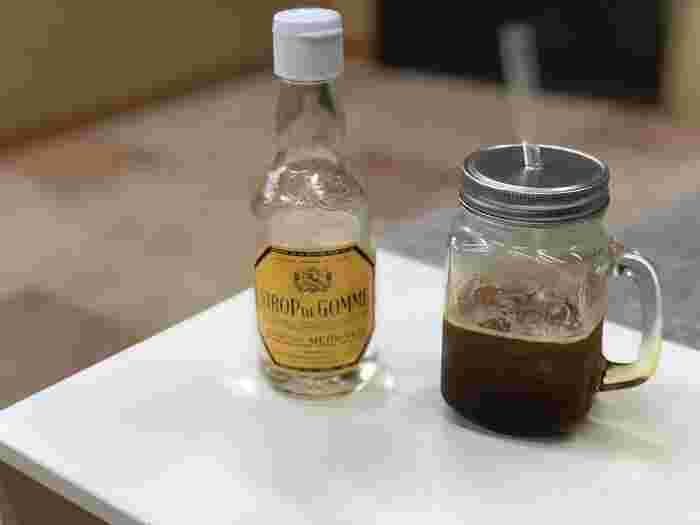 """アイスコーヒーにはグラニュー糖よりも溶けやすいガムシロップがおすすめ。砂糖と水にアラビアガムという添加物を加えて作る甘味料で、ガムシロップの""""ガム""""はアラビアガムからきていますよ。ちなみにホットコーヒーでは甘みを感じにくい特徴があります。"""