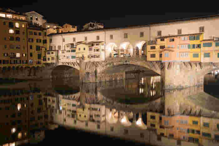夜になると、ヴェッキオ橋はライトアップされ、麗しい姿へと変貌します。漆黒の世闇を背景に、光を浴びて輝くヴェッキオ橋を、アルノ川が鏡のよう映し出し、周囲は幻想的な雰囲気に包まれます。