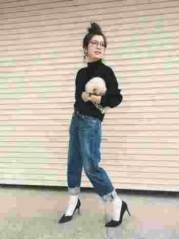 シンプルな黒のトップスにジーンズを合わせたスタイル。切りっぱなしのロールアップしたデニムと薄手の白靴下を合わせた華奢な黒ヒールが女性らしさをアップしていますね。