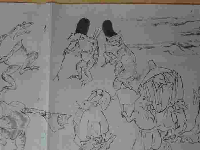 甲・乙・丙・丁の全四巻からなる絵巻『鳥獣人物戯画』は、鳥羽僧正覚猷(かくゆう)の筆とされていますが確証はなく、正式には作者未詳とされ、甲と乙は、平安末期、丙と丁は、鎌倉期の作画と推定されています。  絵巻の中で、特に著名なのは甲巻。 小賢しさや愚かさといった、人々が繰り広げる悲喜劇を、猿や蛙、菟や狐等などの動物たちを擬人化して、ユーモラスに描いた傑作です。この絵巻が描かれたのは、武士が台頭してきた激動の時代。人間模様の洞察力や風刺精神、躍動感のある筆さばきは、当時代に呼応するかの如く、実に旺盛で自由闊達です。