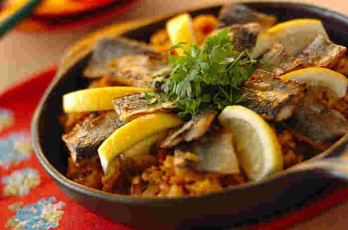 カレー粉で香りと色を付けたパエリアは、炊飯器で炊く簡単レシピ。スキレットに乗せればオシャレなパーティーメニューに。