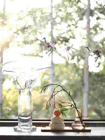 光の差し込む窓辺に鏡餅を飾ると、一日のうちの景色の変化を楽しめます。大きさの違うガラスの花器がバランスよく配置されているところに、センスの良さを感じます。