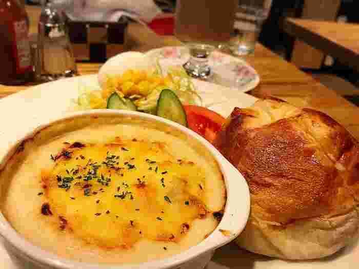ボリュームたっぷりの美味しさそうなグラタンと、ふっくらパン。サラダもついて、朝の時間やランチにぴったり。