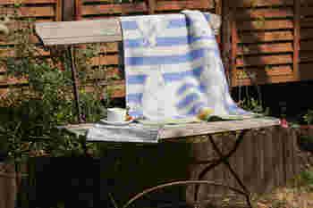 《KLIPPAN ミニブランケット ストライプ ムーミン(65X90cm)》  ウォーレンとムーミンの楽しい絵柄。 白とブルーのボーダーは爽やか。ウォーレンの表情も可愛らしい。