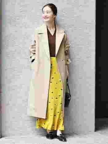 パッと目を引くイエローのスカートは、相性の良いブラウンのトップスを合わせて、秋の華やかコーデに。配色を少しまろやかに中和するために、アウターはベージュをチョイス。