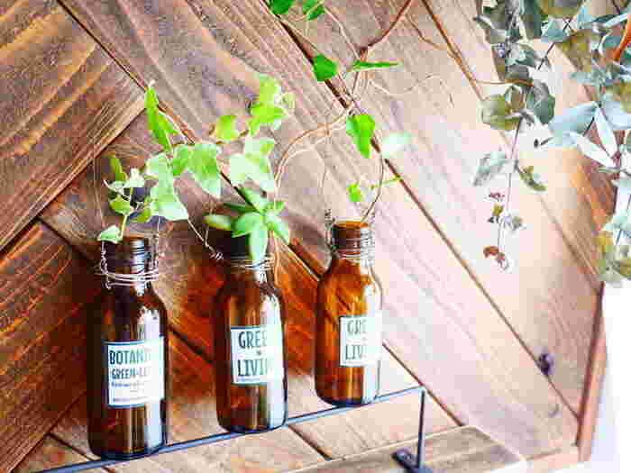 栄養ドリンクの空き瓶にラベルを貼った簡単リメイク。ワイヤーで持ち手を作ると、壁にも吊るせて実用的です。お花やグリーンを飾れば、お部屋の癒しスポットに。