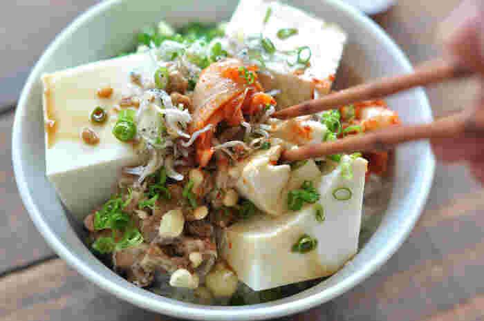 豆腐を切ってご飯にのせ、隙間にキムチやじゃこ、揚げ玉、ネギなどの薬味をのせて醤油をかけるだけの超簡単で美味しいレシピ。滑らかな絹ごし豆腐がおすすめ。のど越しがよくツルンと夏にさっぱり食べられます。冷蔵庫にあるお好きなものでアレンジもOK!