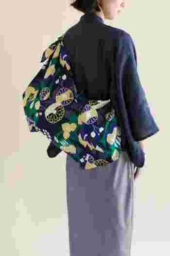 別売りの持ち手に結んでメッセンジャーバッグのように使うこともできますよ。シンプルでベーシックなお洋服には、落ち着いたボタニカル柄のアイテムを。