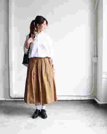 ふわっと広がるシルエットが女性らしいロングスカートに、白シャツをタックインしたスタイルです。シャツにスカートを合わせると、簡単にきちんと感のあるガーリーコーデを作ることができます。スカートの色次第で、大人っぽくもキュートにも着こなせそう。