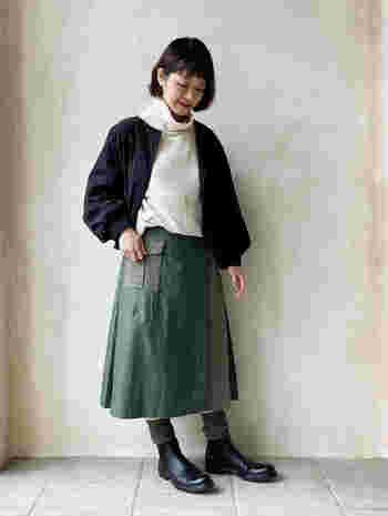 ベージュのハイネックニットに、カーキのスカートと黒のジャケットを合わせたスタイリングです。足元も黒でまとめて、ベージュトップスをクールに着こなしています。