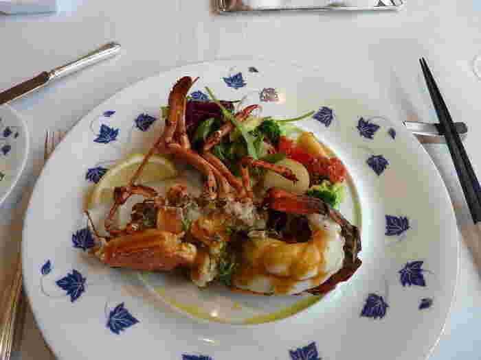 """こちらのお料理は、ホテルオリジナルの""""フレンチジャポネスタイル""""。やさしい味で日本人の味覚に合っていると何度も訪れるリピーターもいるほど高く評価されています。ランチでは、季節の食材を使った3つのコースが中心。テラスに備え付けられた""""ガーデンブロッシュ""""というオリジナルの薪火のかまどで焼き上げるメインディシュも絶品です。写真のオマール海老の薪火焼きも、ここでしか味わえないプロのひと皿。"""