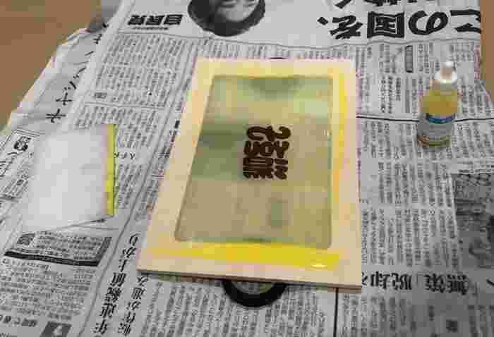 スクイジー(左の白い板)を使用して、スクリーンに描画乳剤を塗ります。