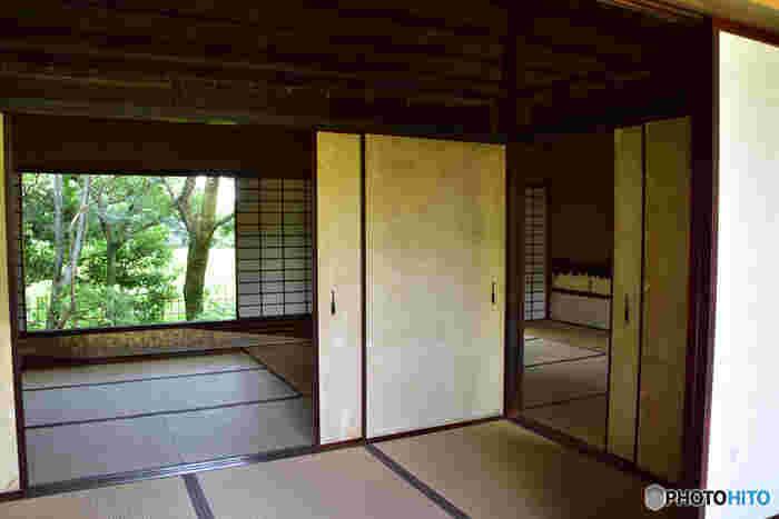 池に面した北側にある茶室は田舎家風の簡素な佇まい。金箔を施したシンプルな襖。その引き手は船の櫂(かい)の形。広大な庭園には船着場の室礼があり、当時としては遊び心のある斬新なデザインの引き手です。