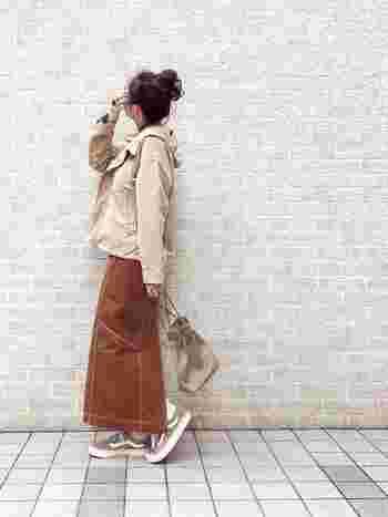 ライトベージュのマウンテンパーカーに、ライトブラウンのロングスカートを合わせた大人カジュアルコーデ。トレンドのラテカラーの組み合わせが温かな印象です。