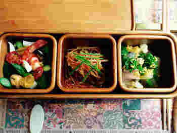 """グルメも忘れてはいけません。東京・南青山「NARISAWA」のオーナーシェフ・成澤由浩さんがプロデュースした「スイーツコース」をいただけます。スイーツの前に、まずは九州の旬の食材をたっぷりと使用した「NARISAWA""""bento""""」を。こちらの弁当箱は、大分・湯布院の木工工房「アトリエとき」が或る列車のためだけに制作されたもの。"""