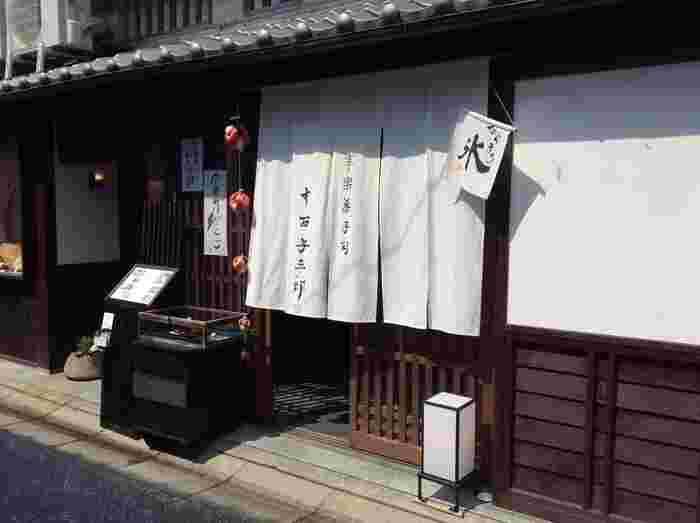 近鉄奈良駅から、もちいどのセンター街を南へ10分ほど歩いていくと、いかにも老舗の風情漂う「寧楽菓子司 中西与三郎」さんの暖簾が見えてきます。店頭には色とりどりの生菓子が並んでおり、その奥が喫茶スペースの六坊庵です。
