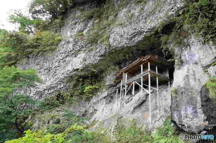 """一体誰が、どうやって、なんの為に――。謎に包まれた国宝のお寺は、その景色も不思議な雰囲気を纏います。  ご紹介するのは、鳥取県の三佛寺にある「投入堂」。岩山の断崖絶壁にあるため、下から眺めるだけしかできず、最も参拝が危険な国宝とされています。  実は、気になる真相はいまだに解明されていません。そして三佛寺には、""""役行者が法力でお堂を小さくし、「えいっ」と断崖絶壁に投げ入れた""""という不思議な言い伝えがあるそうですよ。大人の知的好奇心を刺激する、頼もしい絶景です。"""