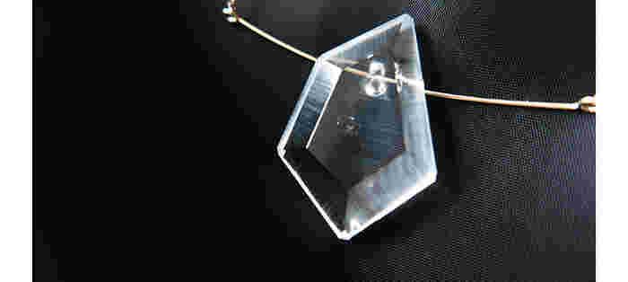 こちらは「Necklace SCRAPER」、耐熱ガラスのネックレスです。デザイナーと職人さんが共に話し合ってできたカッティング、かすれによって光具合が変わるニュアンスなど、こだわりがぎっしり詰まっています。