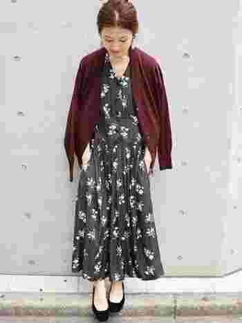 黒の花柄のロングワンピースに、ワインレッドのVネックカーディガンを肩掛けしたスタイル。シックな秋色でまとめた大人な着こなしです。