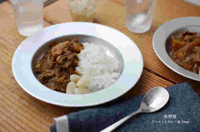 アルマイト加工された松野屋のカレー皿は、適度な深さがあって汁気の多いお料理もきれいに盛り付けることができます。  また、リムの幅が広めにとってあるのも特長のひとつ。熱伝導がよく、アツアツのお料理で熱くなりがちなアルミのうつわでも安心して運ぶことができます。