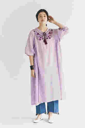 胸元の刺繍と、たっぷりボリューム感のあるシルエットが特徴的なピンクのワンピースです。一枚で着てもサマになりますが、あえてデニムのワイドパンツをレイヤードして、こなれ感のあるコーディネートに。