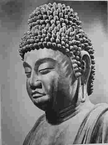 """当代の仏像彫刻は、前代までの乾漆造や塑造、鋳造の仏像が影を潜め、一木造が主流となり、衣紋が波打つような""""翻波式""""と呼ばれる表現様式が多用されるが特徴です。  仏像の素木造への転換については、様々な理由が挙げられますが、山林修行が盛んだった当代の人々が山の木々にも、呪力や霊力を感じていたことによるものが大きいと云われています。 【画像は、神護寺尾本尊「木造薬師如来立像」頭部。】"""