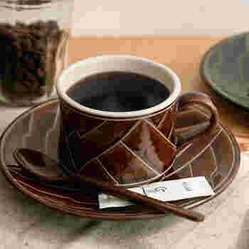 """続いてご紹介するのは、""""やちむん""""で有名な沖縄県の窯元、育陶園が手掛ける「Kamany(カマニー)」のカップ&ソーサーです。伝統的な釉薬と技法を使い、職人さんによって一点一点丁寧につくられています。沖縄らしい大胆な柄と、シックな色合いがおしゃれな雰囲気です。"""
