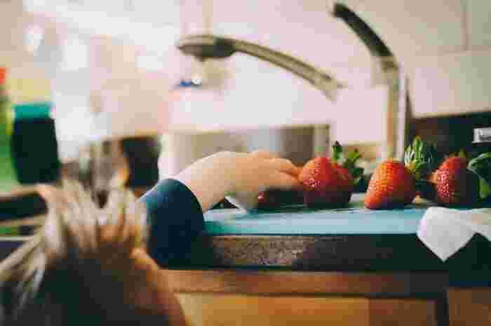 キッチンで、カッティングボード上のいちごに手を伸ばすちびっ子。これが包丁だったら・・・‼