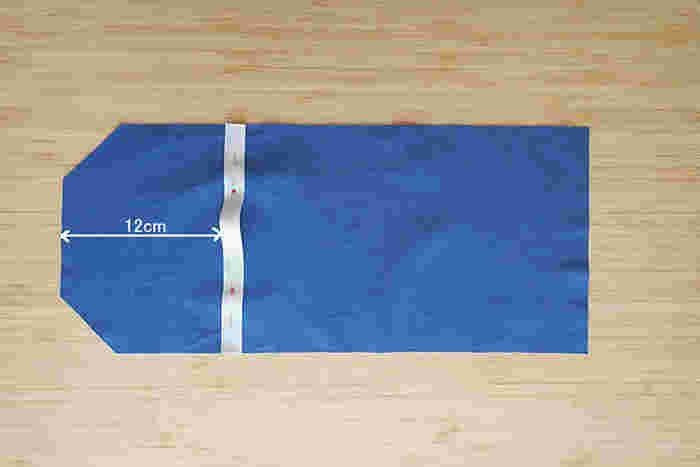隅をカットした方の端から12センチのところに、ベルトを付けます。待ち針で留めたら、ミシンで上下を縫い付けトンネル状にしましょう。