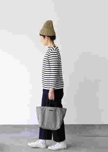 ボーダートップス×黒パンツのシンプルなモノトーンコーデに、グレーのナイロントートを合わせたコーディネートです。しっかりモノトーンでまとめつつ、黒ではなくグレーを選ぶことで程よいアクセントに。ベージュのニット帽が、今っぽさをグッとアップしてくれます。