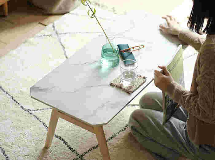 ちょっと珍しい、大理石模様のシートを施したリビングテーブルです。この天板シートは耐久性と耐水性のあるPU塗装が施されているので、テーブルでたくさん作業したいという方にもおすすめ。  キリッとかっこいい大理石デザインですが、こちらのテーブルはさりげなく脚部が天然木。天板の四隅もカットされていて、どこかやさしい印象を放ちます。ナチュラル系のお部屋にも相性がいいですよ。