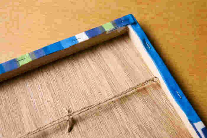 木枠に先がネジになっている「ヒートン金具」を差込み、麻ひもを通すとバランスよく壁にかけられます。