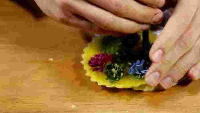 溶けた蝋を型に流したら、ドライフラワーやフルーツを置きます。 リボンを通したい場合は、少し固まってきたところでストローを刺して穴を作ります。