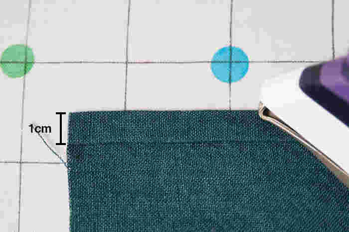 両端をそれぞれ端から1cm折り、さらに1cm折って三つ折りにします。 アイロンで折り目をつけます。