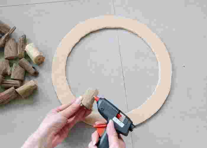次に写真のように流木にグルーガンをつけて、カラーボードに接着していきます。流木は縦・横・斜めなど、隙間を埋めてカラーボードを隠すようにランダムにつけていきましょう。ぐるっと一周接着し終わったら、最後に麻ひもをつけて完成です。直径30センチのカラーボードだと流木3袋が限界なので、もう少し大きいサイズを作りたい方は、合板など強度のあるものを使用してくださいね。