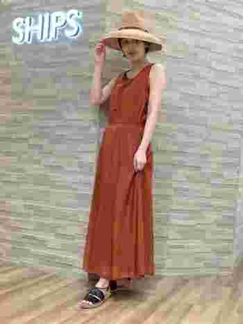 テラコッタカラーのロングワンピースは、つば広めの麦わら帽子とサンダルでリゾート感たっぷり。