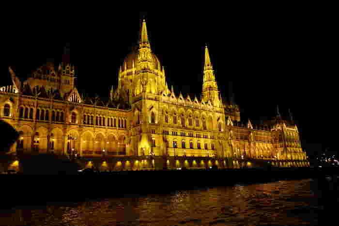 """""""欧州の宝石箱""""、""""東欧のパリ""""など、様々な形容をされるほど美しいのが、ハンガリーの首都ブタペストの夜景です。こちらはドナウ川から国会議事堂を眺めた風景。美しくライトアップされたゴシック様式の国会議事堂は、なんとも幻想的です。"""