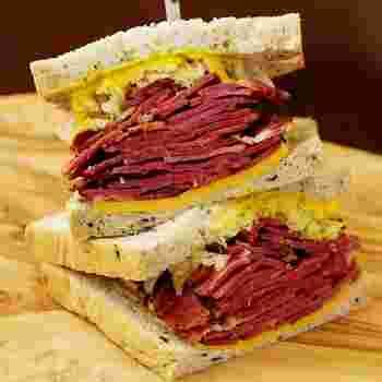 茗荷谷にあるキノーズは、アメリカに住んだ経験のあるオーナーが、本場のおいしいサンドイッチを日本でも…という思いで始めたお店。アメリカンな本格ボリュームサンドが体験できます。写真は、パストラミがたっぷりの「ニューヨークルーベンサンドイッチ」。