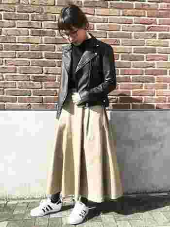 ハリ感のあるベージュのチノスカートに、黒のライダースジャケットは定番の組み合わせ。きりりとした大人っぽさが漂うクールなスタイル。小柄な方でも、アウターをコンパクトにすることで、ボリュームスカートをすっきりと着こなすことができますよ。