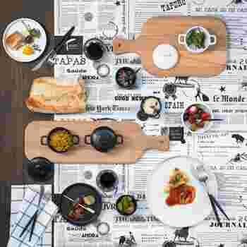 外国の新聞紙をモチーフにしたマットの上に、白と黒のお皿やカトラリーを重ねて。シックでモダンだけど、どこかにぎやかな楽しさもあるのが面白いですね。
