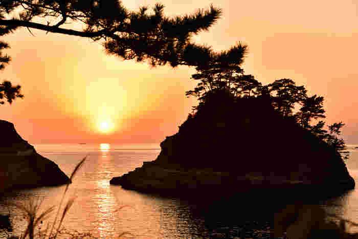 """""""伊豆八景""""の一つに数え上げられる、「堂ヶ島」。岸壁や小島が織り成す、西伊豆で一番美しい景色。駿河湾の水平線の彼方に沈む夕陽。"""