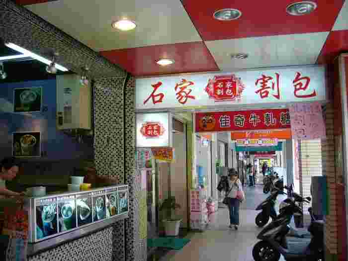 MRT・信義安和駅近くにあり、臨江街夜市(通化街夜市)の中にある「石家割包(シージャグァバオ)」。1953年創業という、割包の老舗として有名です。 こちらの「通化旗艦店」の店舗が本店にあたります。そのほか、台北市内に、民生西路にある「寧夏店」、民生東路にある「民生東店(源石石家割包)」などの支店がありますよ。
