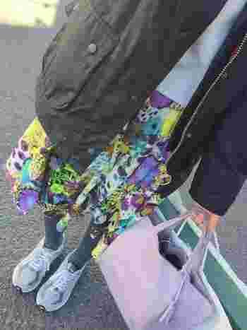 オーソドックスなブラックアウターは、ビビッドな柄スカートと組み合わせてお洒落にコーデ。