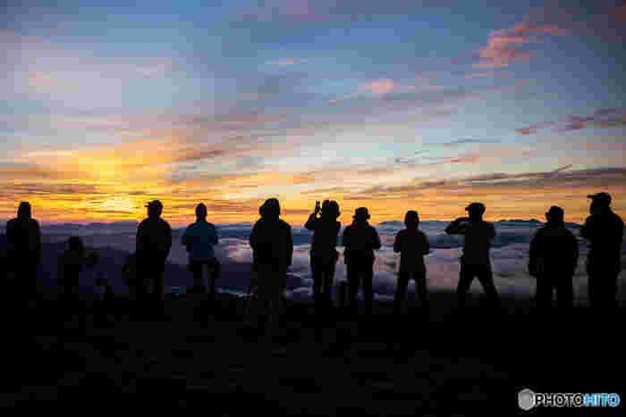 登山仲間と北アルプス・乗鞍岳の頂上から朝焼けを眺める。天候が変わりやすい高山での幸福な【経験の共有】。